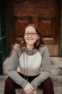 Author Pic sitting on stone steps in front of a wooden door